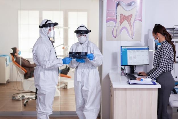 치과 진료실에서 코로나바이러스로 전 세계적으로 유행하는 동안 ppe 복장을 한 구강학 팀이 환자 엑스레이를 들고 사회적 거리를 유지합니다.