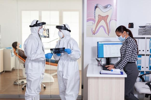 치과 진료실에서 코로나바이러스로 전 세계적으로 유행하는 동안 ppe 정장을 입은 구강학 팀 ...