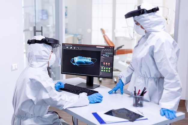 Stomatology team looking at patient jaw on monitor screen dressed in ppe suit. medical specialist wearing protective gear against coronavirus during global outbreak looking at radiography in dental of