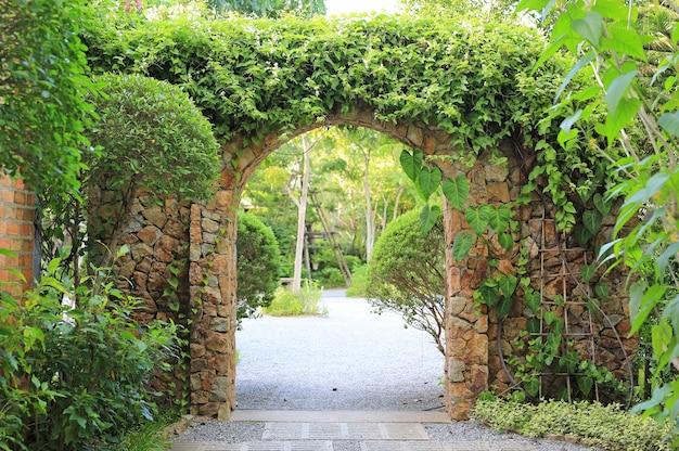 Входные ворота из каменной арки покрыты плющом. арка в парк.