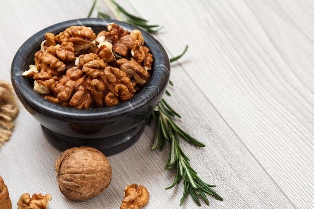 껍질을 벗긴 호두와 로즈마리가 나무 배경에 있는 돌 그릇. 유용한 영양가 있는 단백질 제품. 평면도.