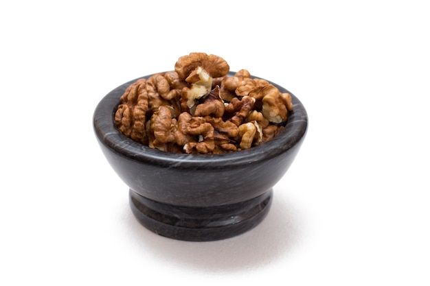 흰색 격리된 배경에 껍질을 벗긴 호두가 있는 돌 그릇. 유용한 영양가 있는 단백질 제품. 평면도.
