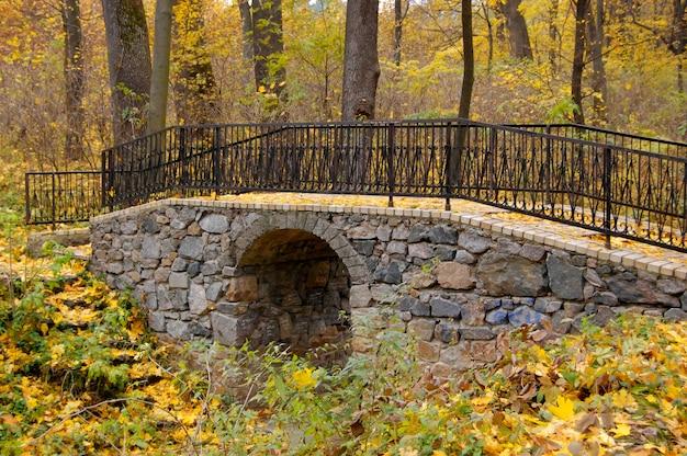 黄色の木のヴィンテージの秋を手すりの石の橋。