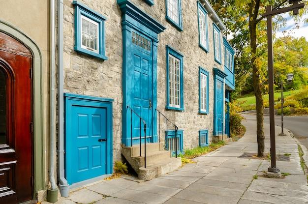 파란색 셔터가 있는 타운하우스의 석조 건물