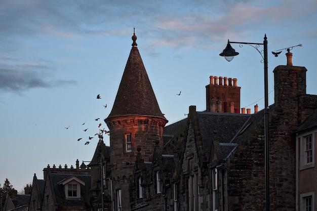 Каменные дома на улице старинного шотландского городка с башней, фонарем и летающими птицами над т ...