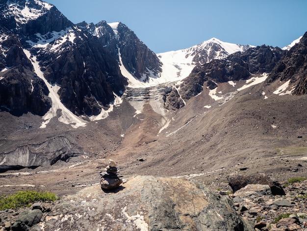 石のケアン。山の背景にある石のケアン、道の標識。