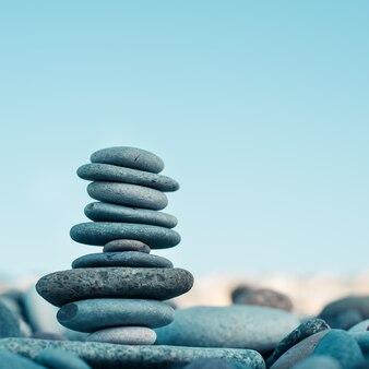 緑のぼやけた背景、小石、石の石のケアン。コンセプトバランス