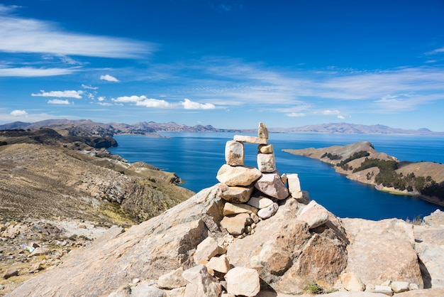 Stone cairn with scenic dramatic landscape on island of the sun, titicaca lake, among the most scenic travel destination in bolivia.