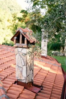 Каменный дымоход на черепичной крыше на фоне зеленой ветки дерева