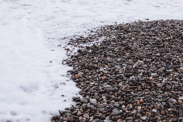 白い海の泡と石の海岸線