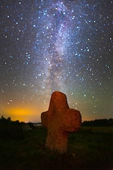 별이 빛나는 하늘 아래 오래된 묘지의 돌 십자가