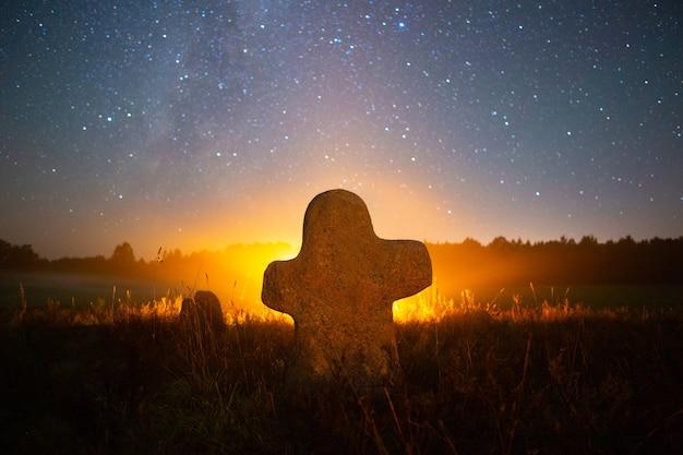 별이 빛나는 하늘 아래 오래된 묘지의 돌 십자가 프리미엄 사진
