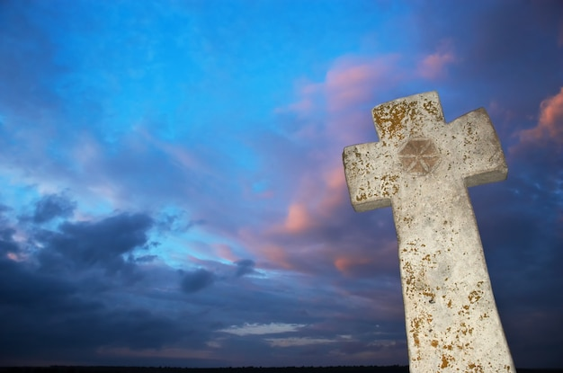 Stone cross on dark sky background