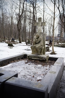 Stone cross on grave with statue of crying woman. in snowbound cemetery among leafless trees - smolenskoe lutheran cemetery, russia, st. petersburg, march 2021