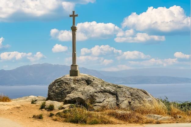 スペイン、ガリシアのフィステーラ海岸の崖の上の石の十字架。