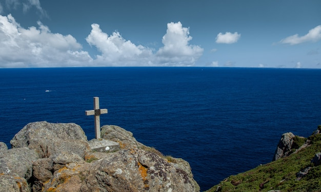 Stone cross on top of a hill facing the sea in galicia, spain