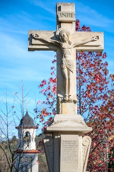 Stone cross with crucified jesus christ and engraving in curchi monastery. gates, tree with red rare leaves. good weather in moldova