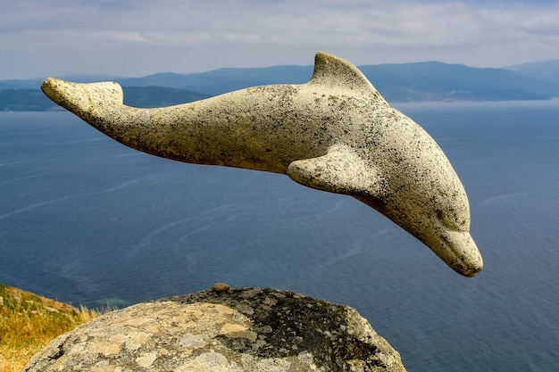 Stone dolphin sculpture on a cliff in galicia. spain.