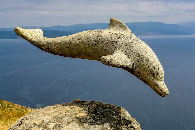 갈리시아의 절벽에 있는 돌 돌고래 조각. 스페인. 프리미엄 사진
