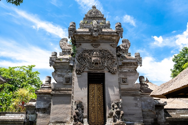 Stone entrance to a hindu temple with a wooden door