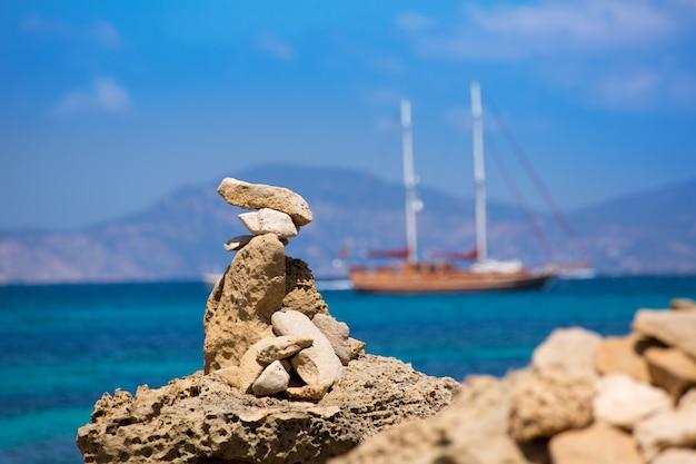 Stone figures on beach shore of illetes beach in formentera