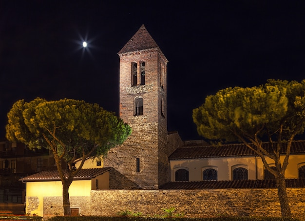 Stone fortress with a bell tower at night