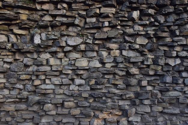 Каменная стена из серого гранита армированная цементом для цельного каркаса из камней разных размеров и форм.