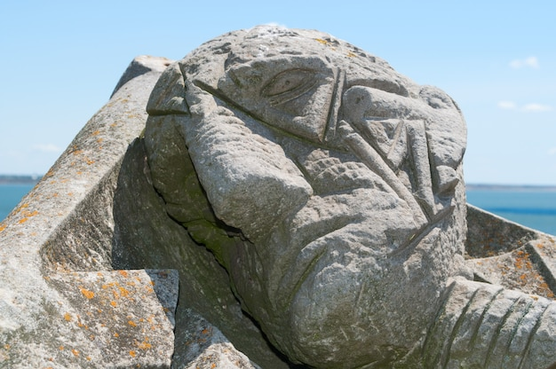 Stone head of a man close up against the sky