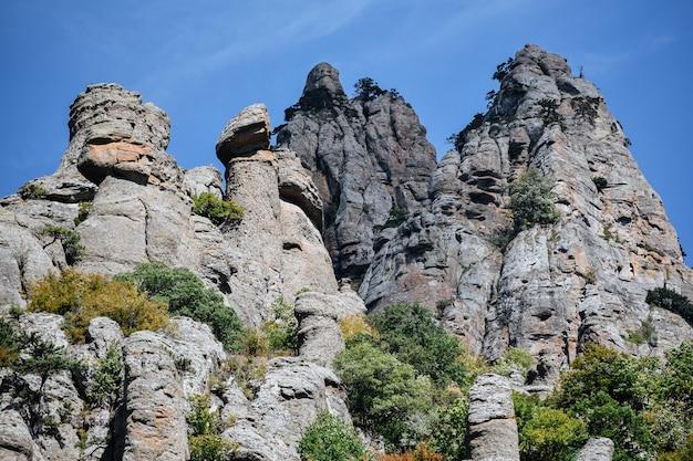 Каменные холмы и горы на фоне голубого неба