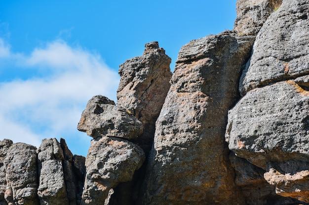 흰 구름과 푸른 하늘을 배경으로 돌 언덕과 산