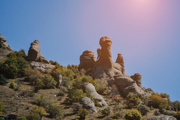 Каменные холмы и горы с зелеными деревьями и кустами на фоне голубого неба.