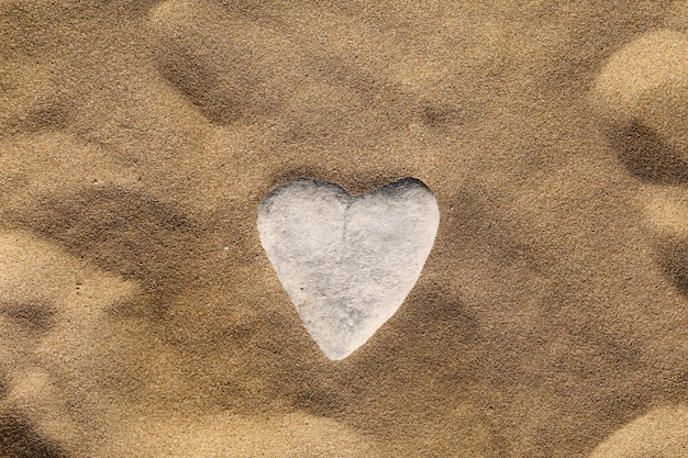 Камень в форме сердца на песке. морская песочная стена, обои. концепция поздравительной открытки день святого валентина, свадьба, медовый месяц или любовь