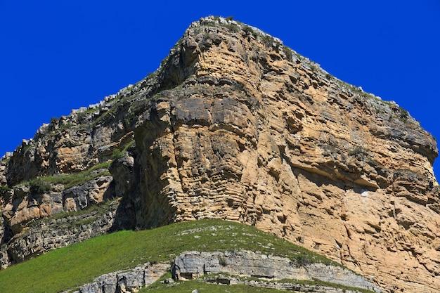 青い空を背景にした岩だらけの尾根の石の棚。