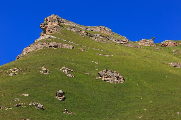 Stone ledge of a rocky ridge against the blue sky.