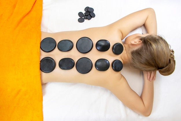 Stone massage top view of beautiful young woman lying on front with spa stones on her back. beauty treatment concept