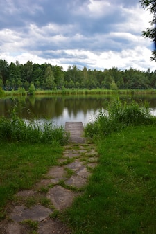 A stone path leads to a small wooden pier on the banks of a picturesque river.