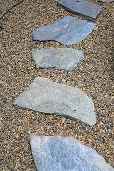 小石の背景を持つ公園の石の道。