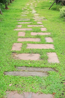 Stone pathway in the park with green grass around.