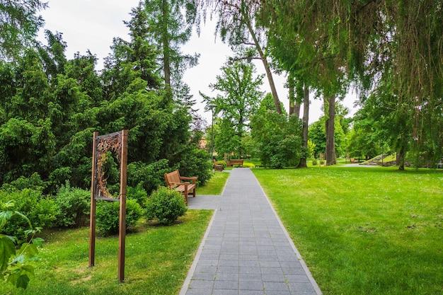 공원 양쪽에 녹색 잔디와 나무가 있는 돌 포장된 통로.