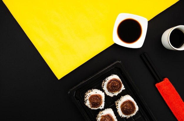 Stone plate with sushi rolls on a black background with soy sauce bowl on yellow background