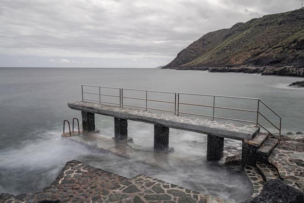 Каменная платформа с металлической лестницей на берегу атлантического океана, ла калета, эль йерро, канарские острова, испания