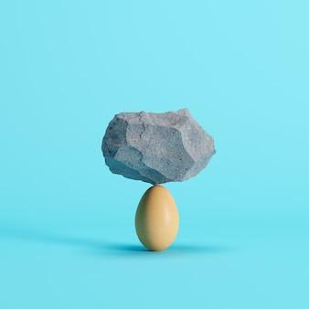 Stone put on egg on blue background