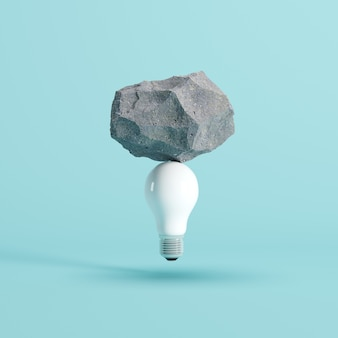 Stone put on white light bulb floating on blue background