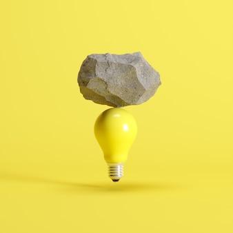 Stone put on yellow light bulb floating on yellow background