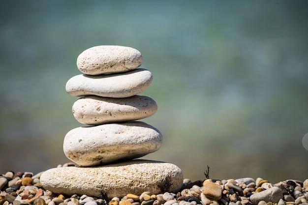 海のクローズアップの背景にある石のピラミッド。心を落ち着かせる海。小石の海岸。