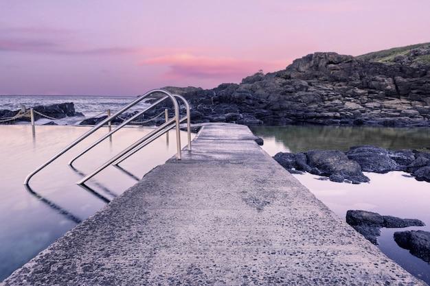 Каменная дорога в образовании воды на берегу моря во время заката