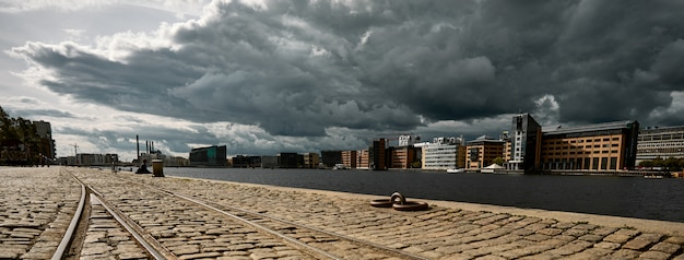 Stone road surrounded by buildings under a dark cloudy sky