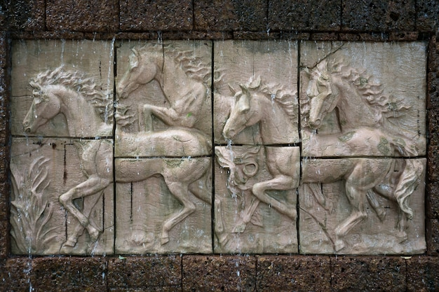 Каменная скульптура лошадей на стене с водопадом