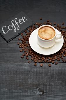暗い木製のテーブルにエスプレッソとコーヒー豆のチョーク手書きサインカップと石のサービングボード