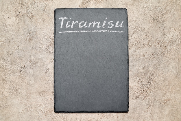 Stone serving menu board with chalk handwritten tiramisu sign
